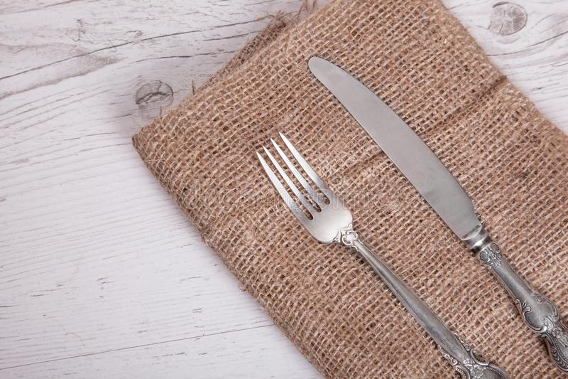 葡萄酒银色碗筷刀子和叉子在餐巾 免版税图库摄影