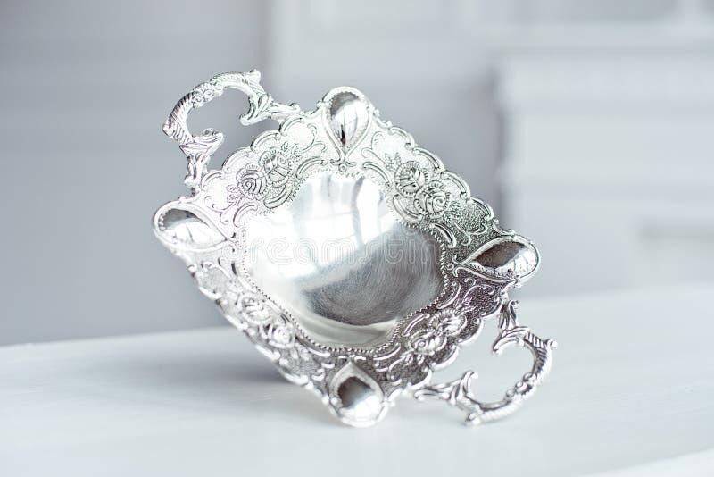 葡萄酒银镀了碗在室内白色桌上的焦点盘 库存照片