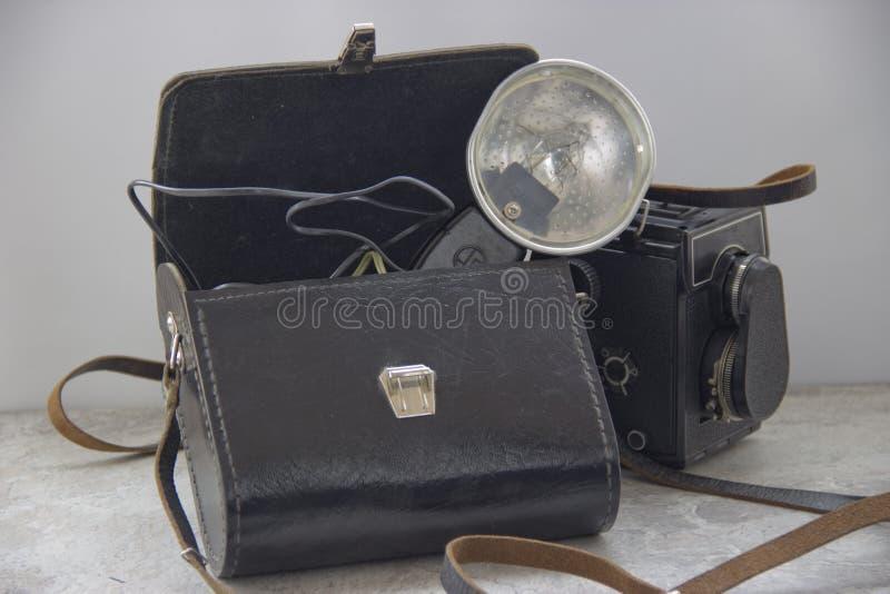 葡萄酒闪光和照相机在桌上 免版税图库摄影