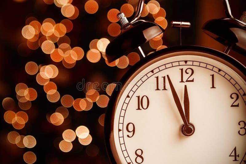 葡萄酒闹钟显示午间或午夜 它是十二个o `时钟、圣诞节和bokeh,假日新年好欢乐conce 免版税库存图片
