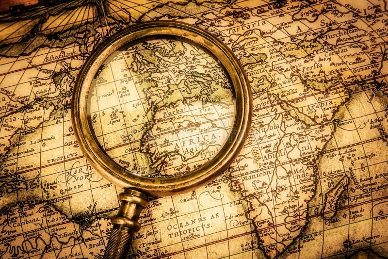 葡萄酒放大镜在一张古老世界地图说谎 库存图片