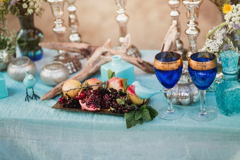 葡萄酒静物画:与花瓶的被装饰的设计师桌花和装饰在绿松石和蓝色样式 室外装饰构成 库存照片