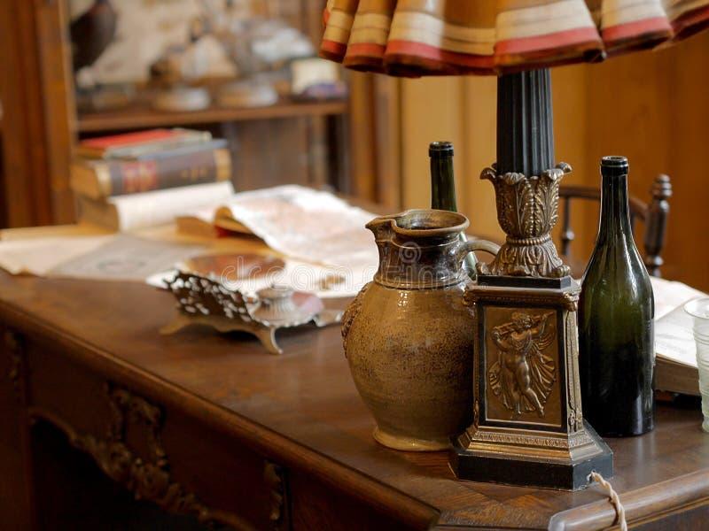 葡萄酒项目、水罐和文件在老办公桌上 库存照片