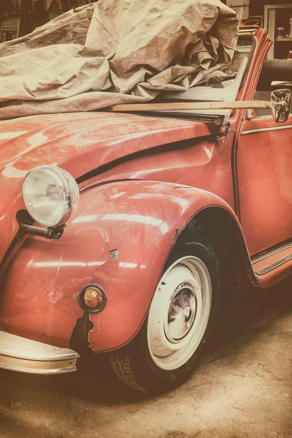 葡萄酒风化了在一个老车库的经典红色汽车 免版税库存图片