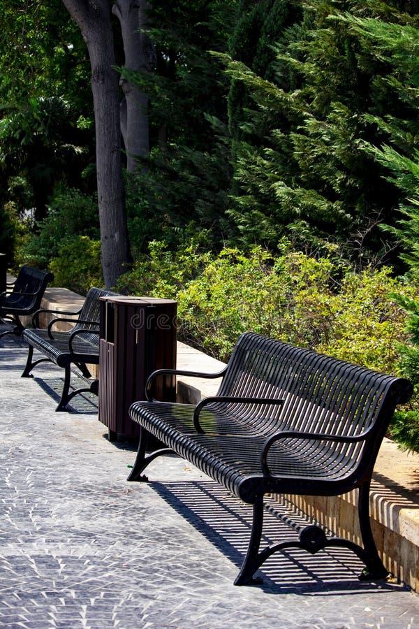 葡萄酒黑benchs在公园 免版税库存图片