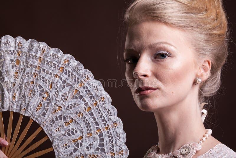 葡萄酒维多利亚女王时代的礼服的妇女有一个东方爱好者的在手中 免版税图库摄影