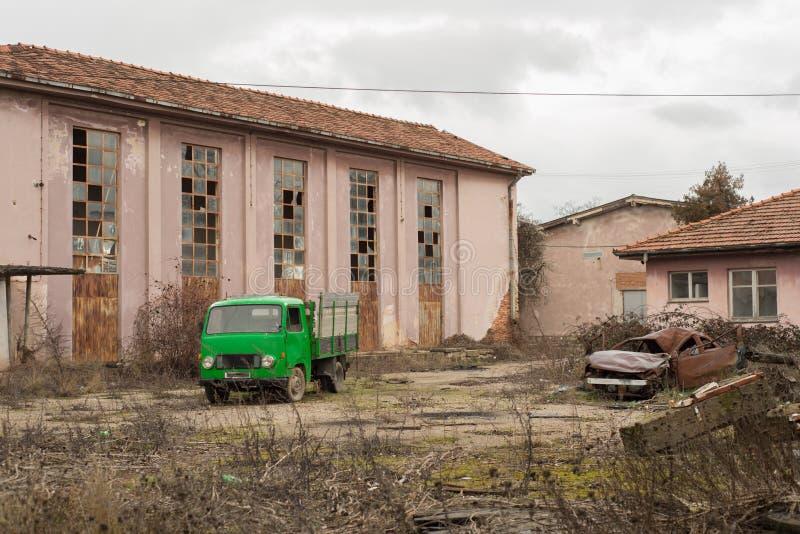 葡萄酒绿色卡车在被放弃的工厂后院 免版税库存图片
