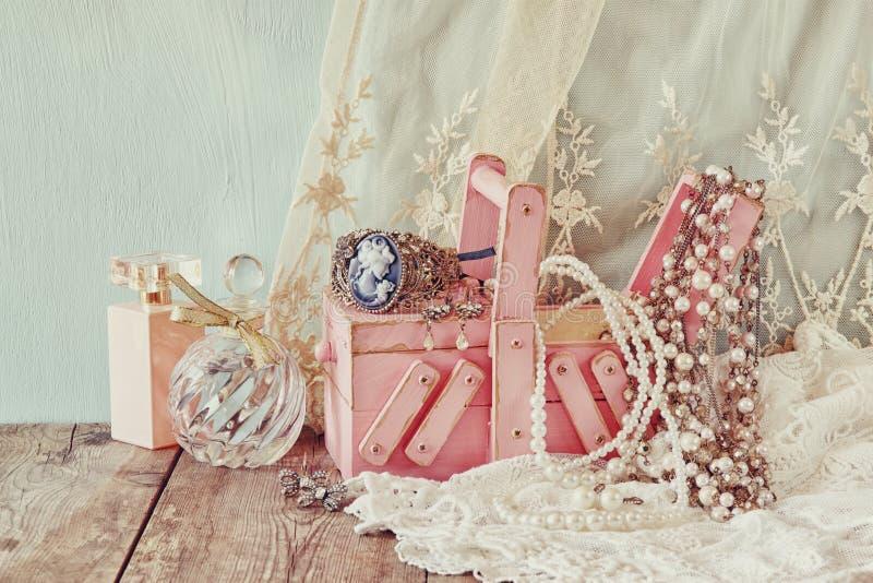 葡萄酒jewelelry,古色古香的木首饰盒和香水瓶在木桌上 被过滤的图象 免版税库存图片
