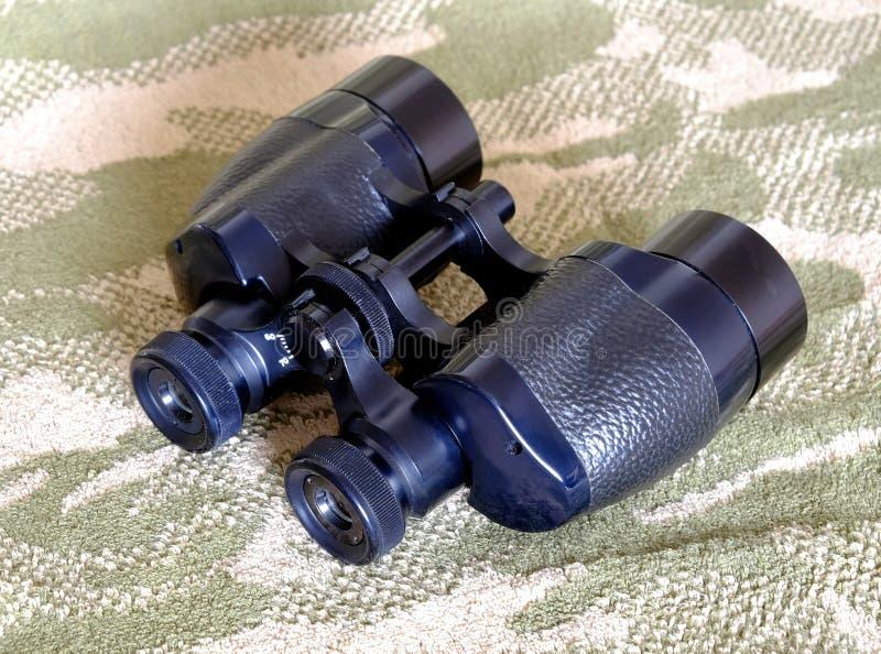 葡萄酒Porro棱镜在伪装背景的黑色双筒望远镜 库存图片