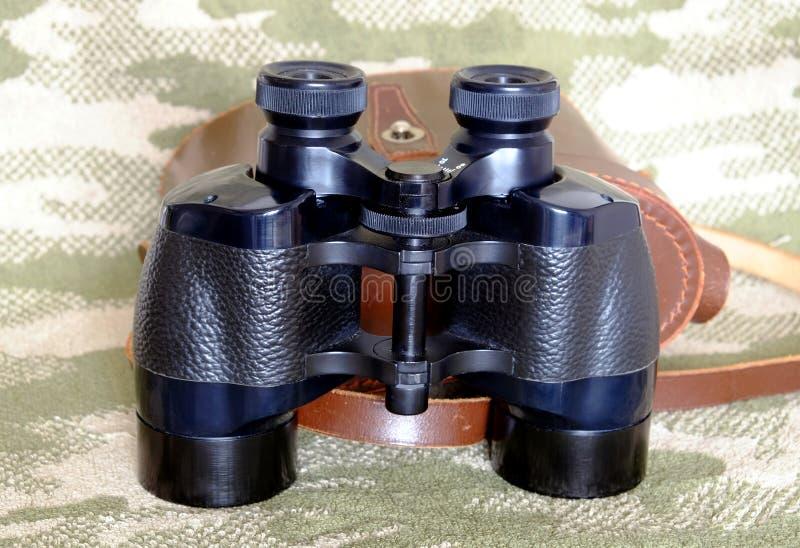 葡萄酒Porro棱镜有案件的黑色双筒望远镜在伪装背景 库存照片