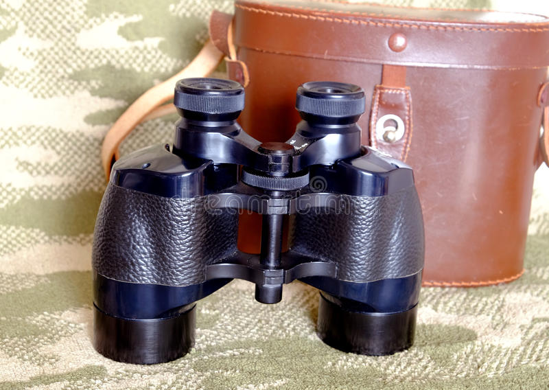 葡萄酒Porro棱镜有案件的黑色双筒望远镜在伪装背景 库存图片