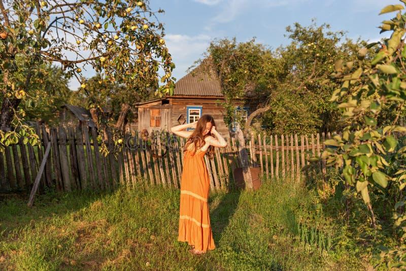 葡萄酒sarafan礼服的少妇在平静的镇静日出的一棵土气苹果树站立伸她的手 免版税库存照片