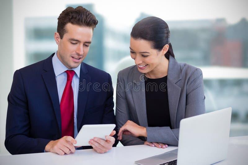 董事的综合图象谈论在片剂,当坐反对白色背景时 免版税库存照片