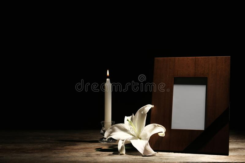 葬礼照片框架、灼烧的蜡烛和白百合 库存照片