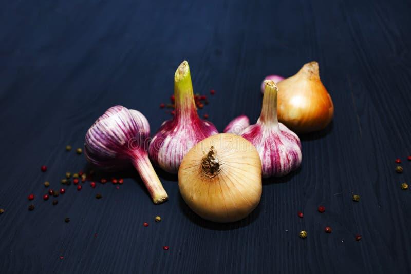 葱,大蒜,在黑木背景的色的胡椒豌豆 图库摄影