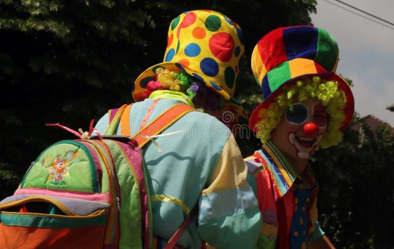 蒂米什瓦拉,罗马尼亚06 25 作为小丑打扮的2017两年轻人戴五颜六色的衣裳、卷曲假发和大帽子笑快乐 库存照片