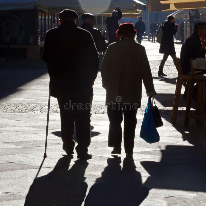 蒂米什瓦拉,罗马尼亚-12 13 2016对手拉手老夫妇步行在一条街道上在老市中心到充分的阳光里 图库摄影