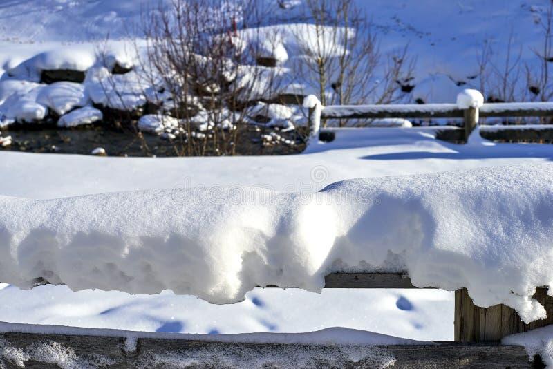 蒂罗尔阿尔卑斯冬天风景:积雪的木栏杆,背景的山小河 图库摄影