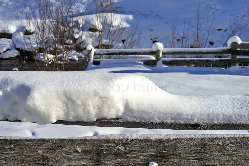 蒂罗尔阿尔卑斯冬天风景:积雪的木栏杆,背景的山小河 库存图片