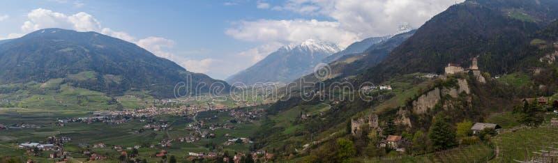 蒂罗尔Meran城堡在谷里面和阿尔卑斯全景与城堡Brunnenburg的  提洛尔村庄,省波尔查诺,波尔扎诺自治省, 免版税库存图片
