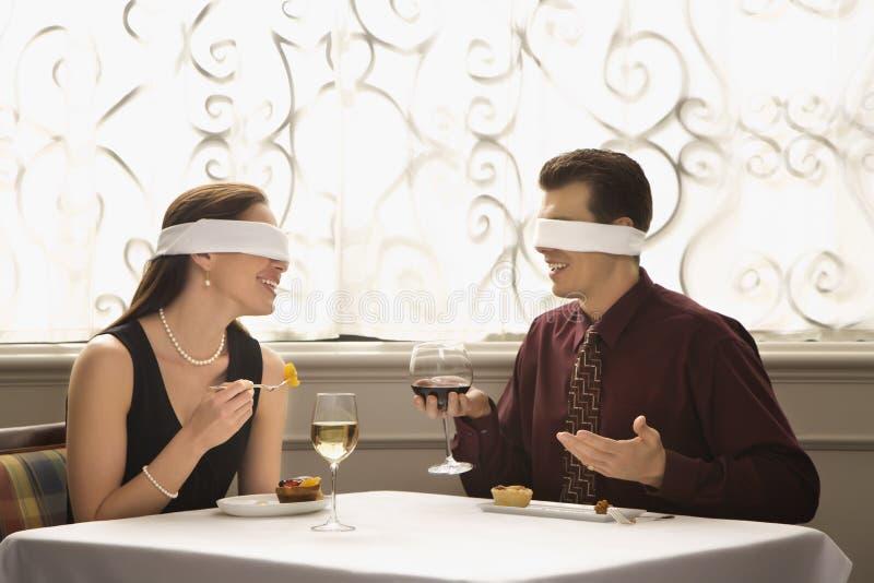 蒙住眼睛夫妇用餐 免版税图库摄影