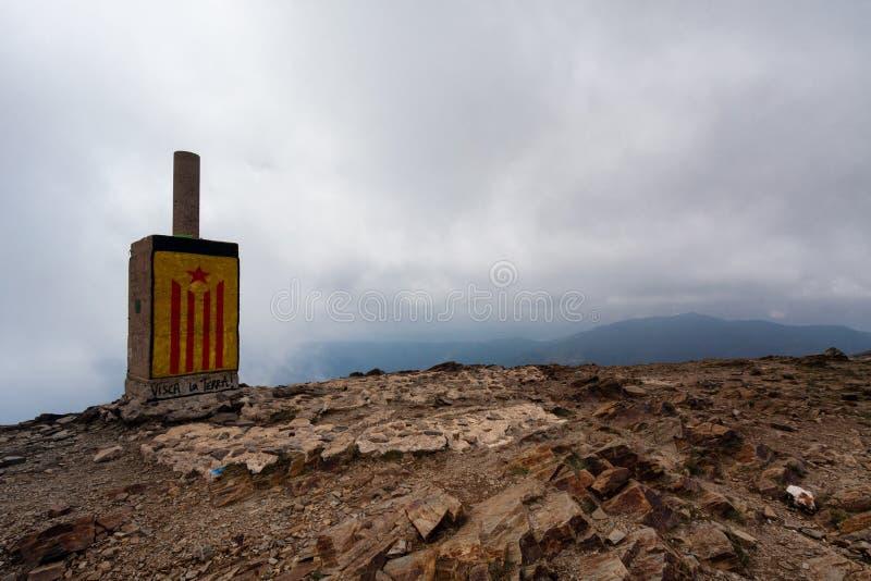 蒙塞尼,西班牙, 2016年11月国家公园:与分离主义者旗子Estelada roja街道画的纪念碑在山顶部 免版税库存照片