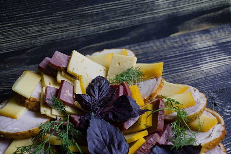 蒜味咸腊肠、切的火腿和乳酪沙拉和菜 紧压香肠和被治疗的肉在一张欢乐桌上 库存照片