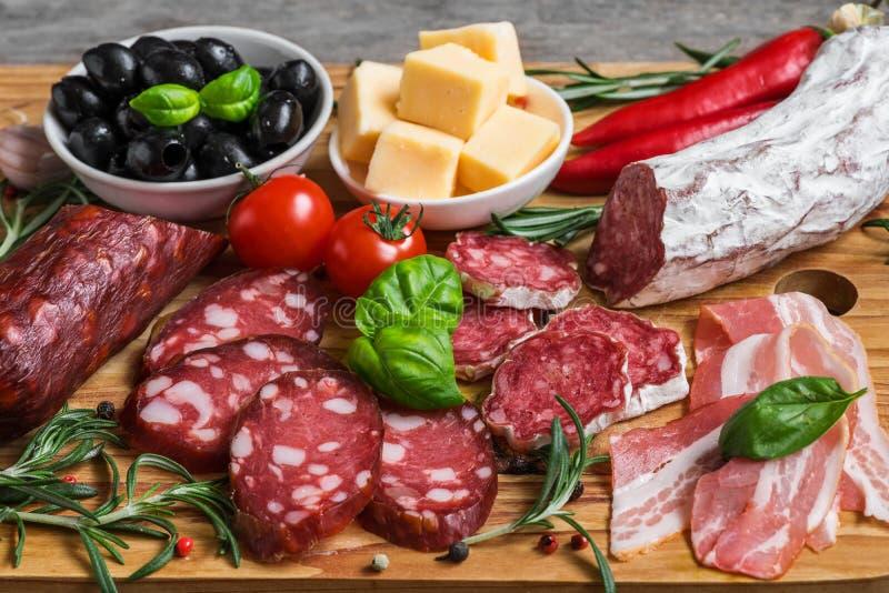 蒜味咸腊肠、切的烟肉、香肠、乳酪、橄榄、蕃茄和草本 肉在木桌上的开胃小菜盛肉盘 免版税库存照片