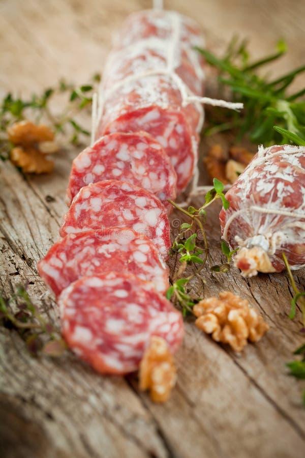 蒜味咸腊肠香肠切用胡椒、大蒜和迷迭香在切板在木桌上 免版税图库摄影