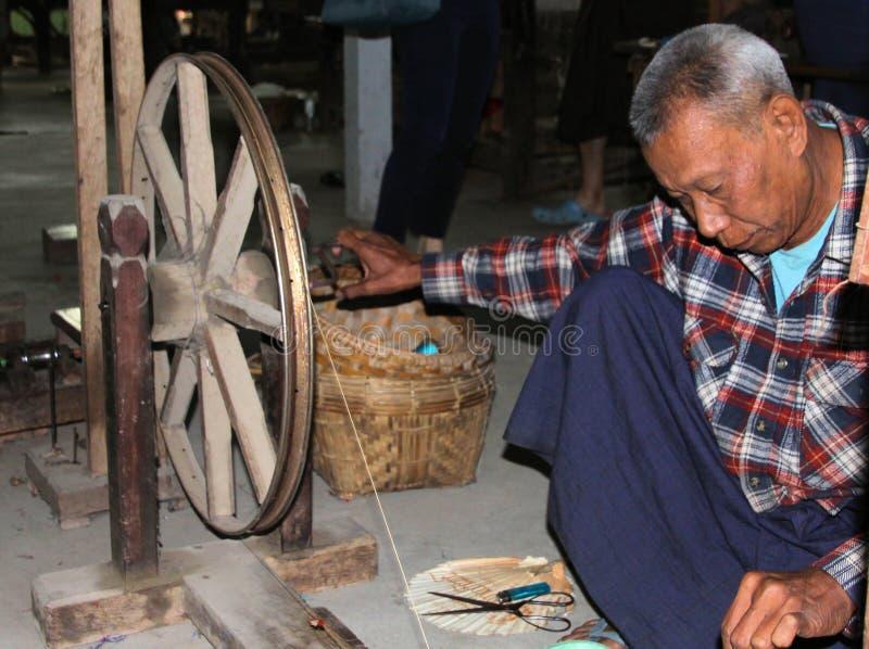 蒲甘,缅甸- 12月21 2015年:转动在与古老木轮子的一个简单的小屋前面的老缅甸人 免版税图库摄影