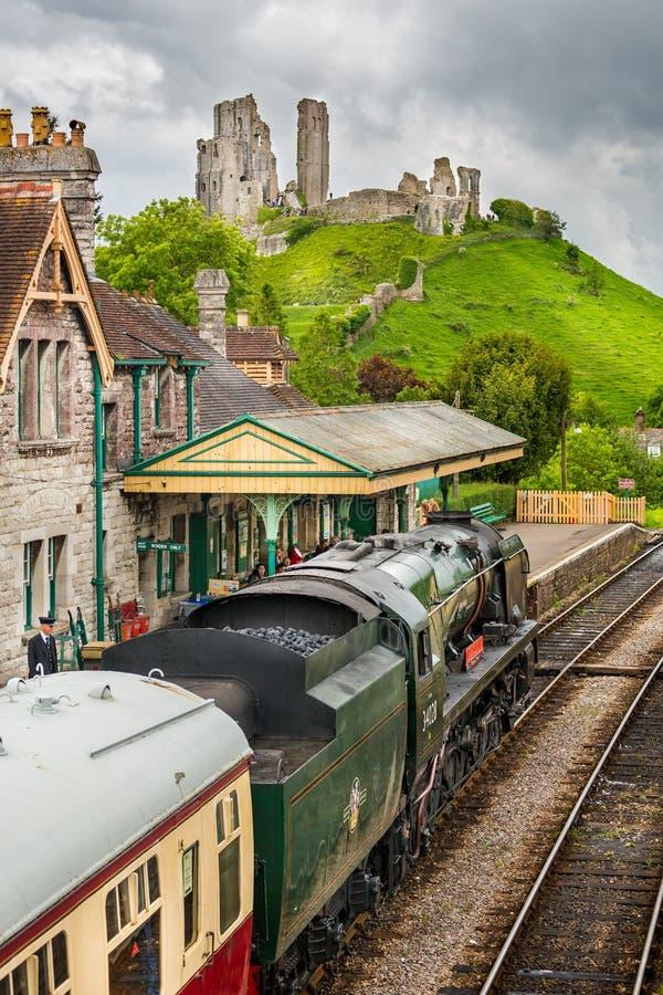 蒸汽机车Eddystone拉扯入Corfe与Corfe城堡的城堡驻地的在Corfe采取的背景中,多西特,英国 免版税库存照片