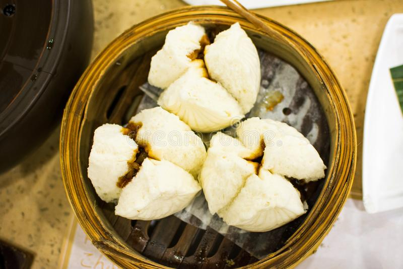 蒸的小圆面包用烤猪肉在竹火轮服务 免版税库存图片