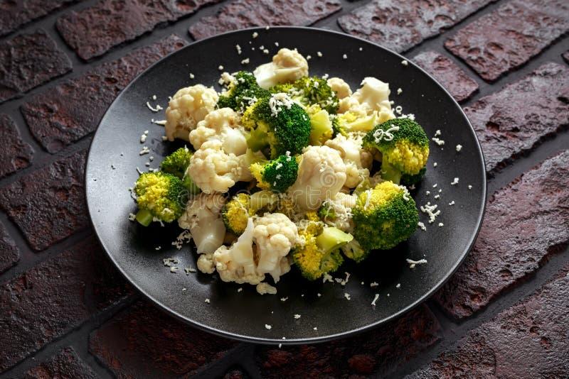 蒸的硬花甘蓝,花椰菜沙拉用在一个黑色的盘子的帕尔马干酪 健康概念的食物 图库摄影