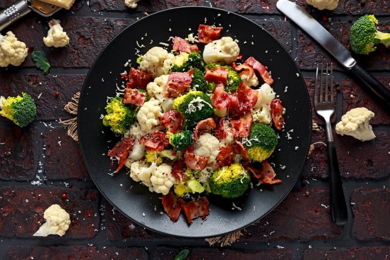 蒸的硬花甘蓝,花椰菜沙拉用烟肉,在一个黑色的盘子的帕尔马干酪 健康概念的食物 免版税库存图片