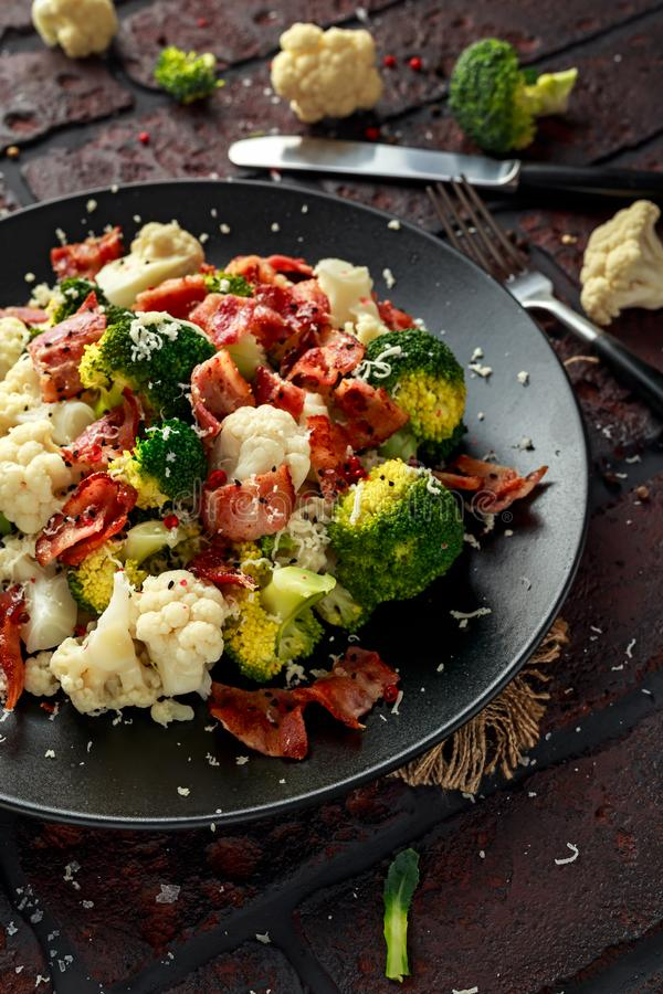 蒸的硬花甘蓝,花椰菜沙拉用烟肉,在一个黑色的盘子的帕尔马干酪 健康概念的食物 库存图片