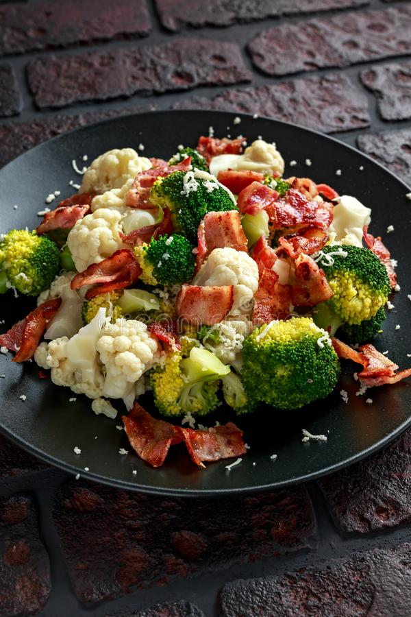 蒸的硬花甘蓝,花椰菜沙拉用烟肉,在一个黑色的盘子的帕尔马干酪 健康概念的食物 库存照片