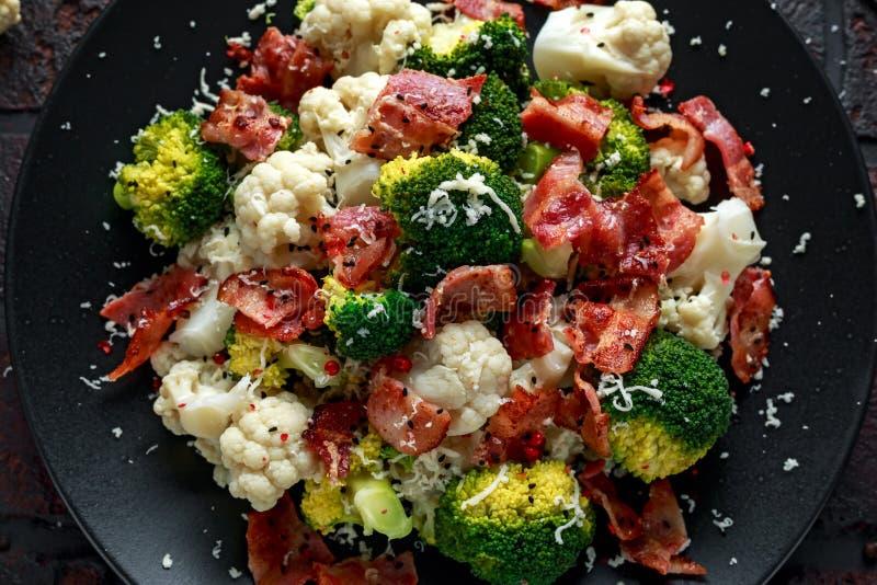 蒸的硬花甘蓝,花椰菜沙拉用烟肉,在一个黑色的盘子的帕尔马干酪 健康概念的食物 图库摄影