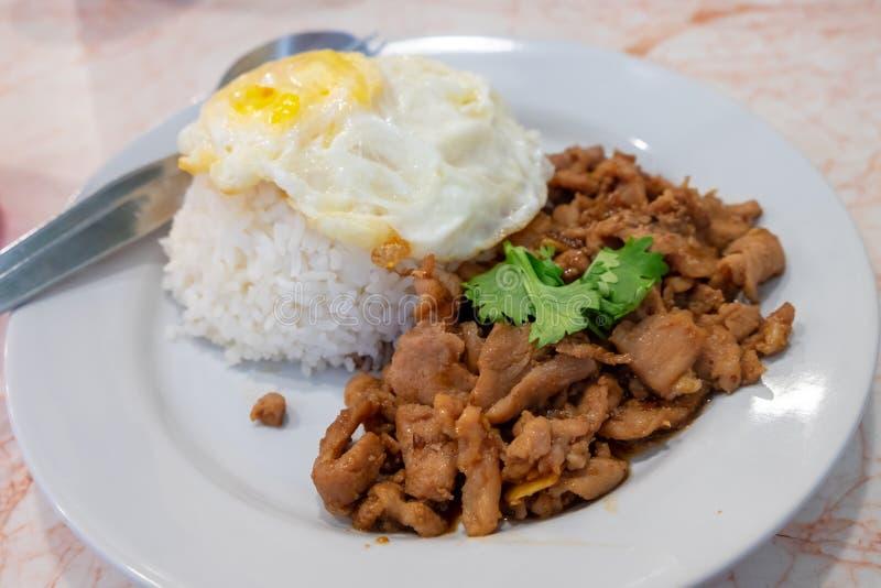 蒸的米冠上了用一个煎蛋用混乱油煎的猪肉用在盘投入的大蒜 免版税库存照片