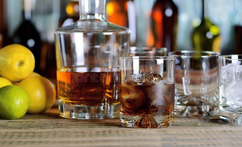蒸馏瓶和杯与冰的威士忌酒 库存照片