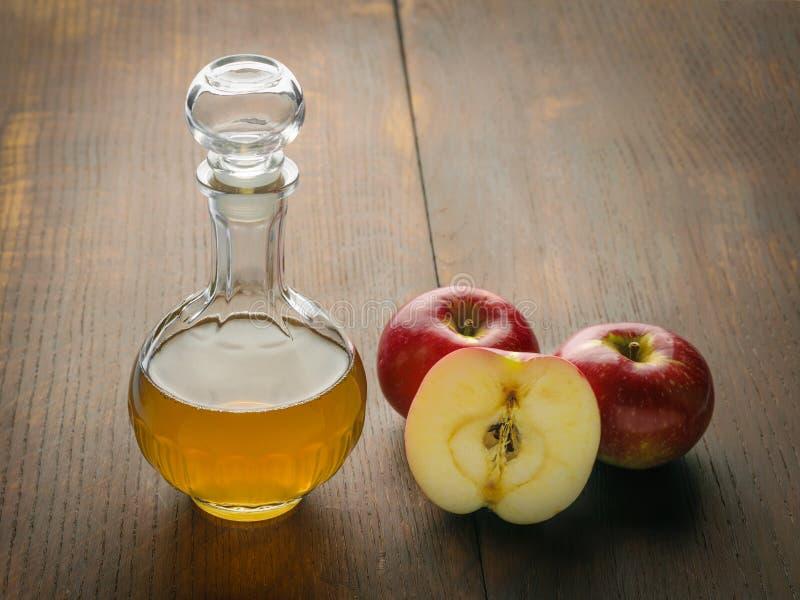 蒸馏瓶在一张木桌上的苹果汁醋用红色苹果 免版税图库摄影