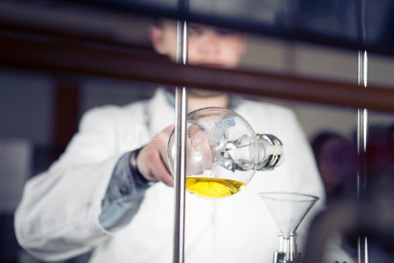 蒸馏的实验室设备 分离组分物质从混合液体 举行配药的研究员唔 免版税库存照片