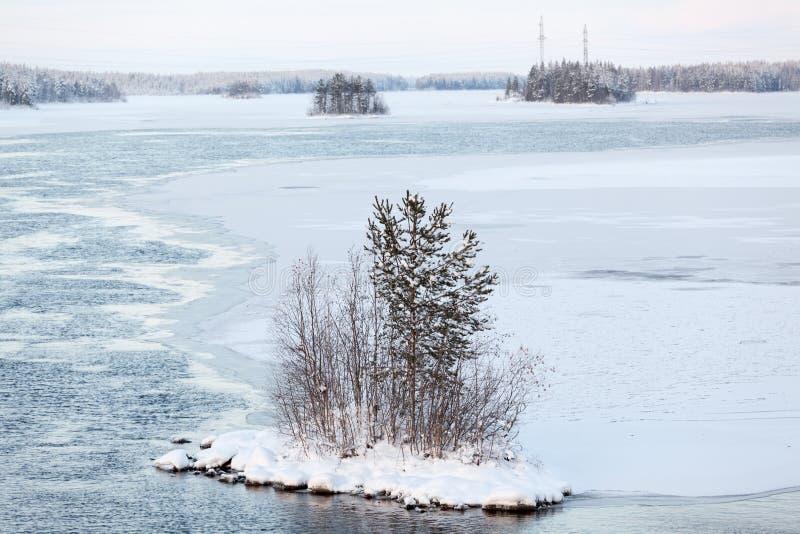 蓄水库大水池与小河的在冰,流程,冬天季节中部的小海岛下  卡累利阿的湖和河 库存图片