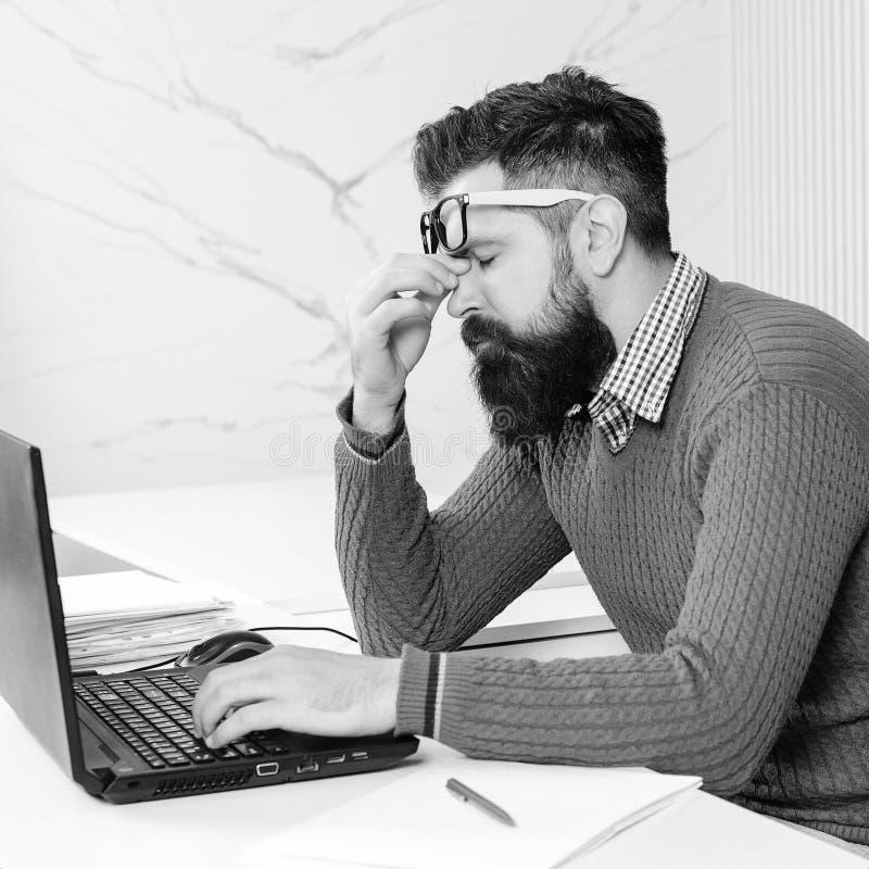蓄胡子的人在笔记本上工作 他工作地的累人 蓄胡子的男人在办公室工作过度 库存图片
