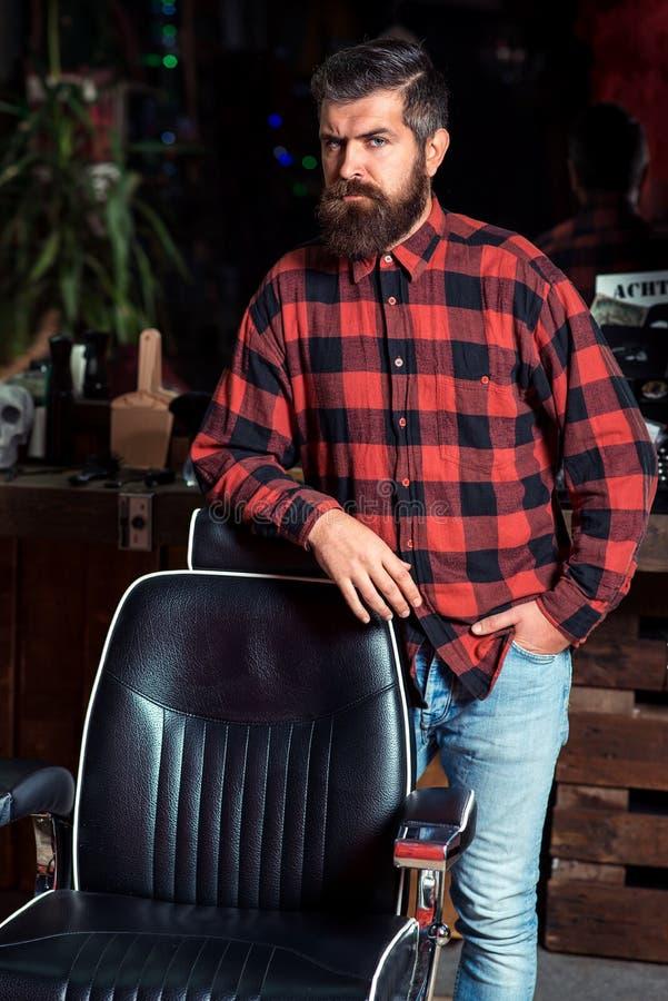 蓄须男 理发店的时尚男士 时髦的理发店 留着胡子、穿着格子衬衫的时尚男士站在老古董附近 库存照片