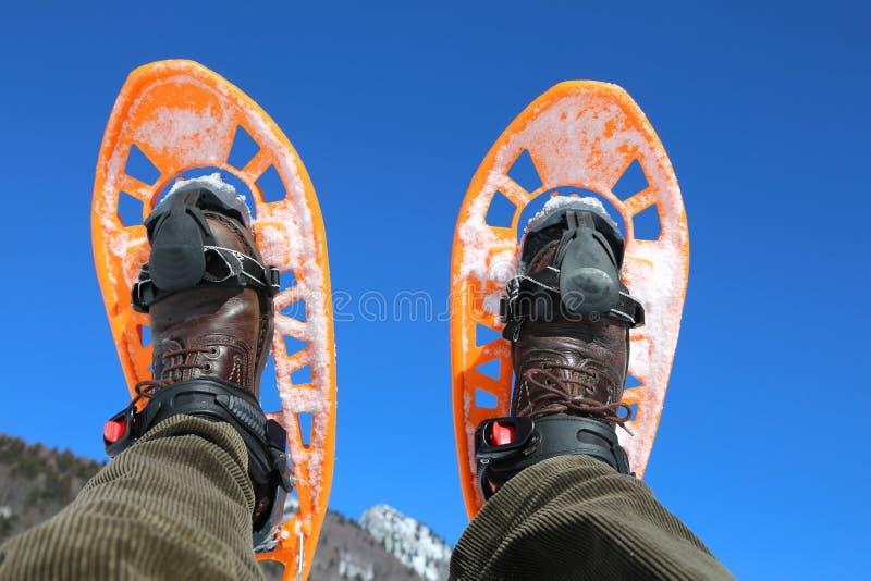 蓝天和一个人有雪靴的 免版税库存图片