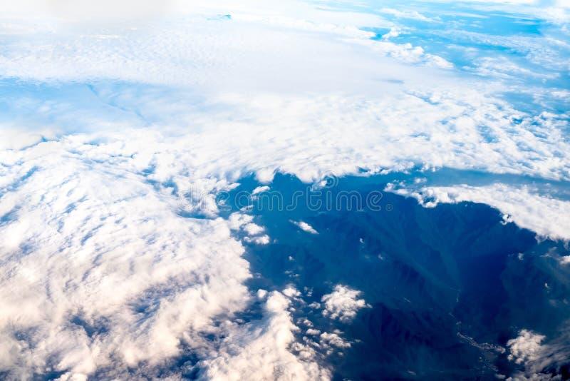 蓝天和云彩和山顶视图从飞机窗口, Na 免版税库存照片