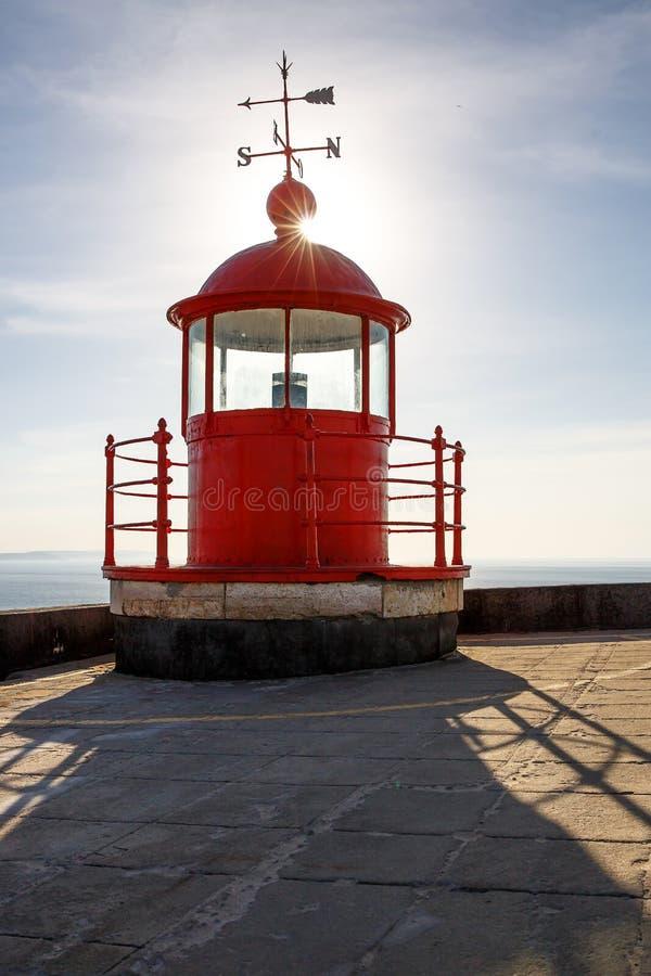 蓝天和海背景的红色灯塔矿灯房 免版税库存照片