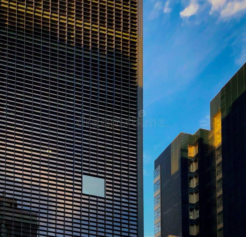 蓝天摩天大楼办公室窗口与城市企业大厦 免版税库存照片