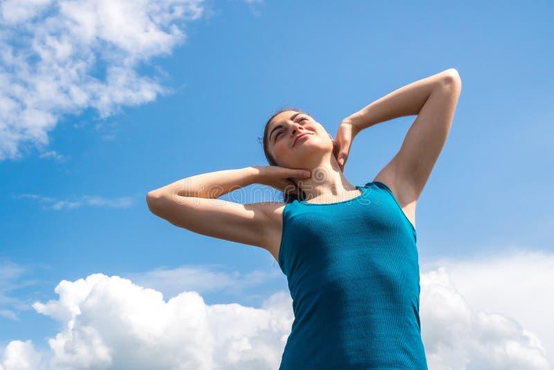 蓝天背景的美丽的体育女孩在锻炼以后 免版税库存照片