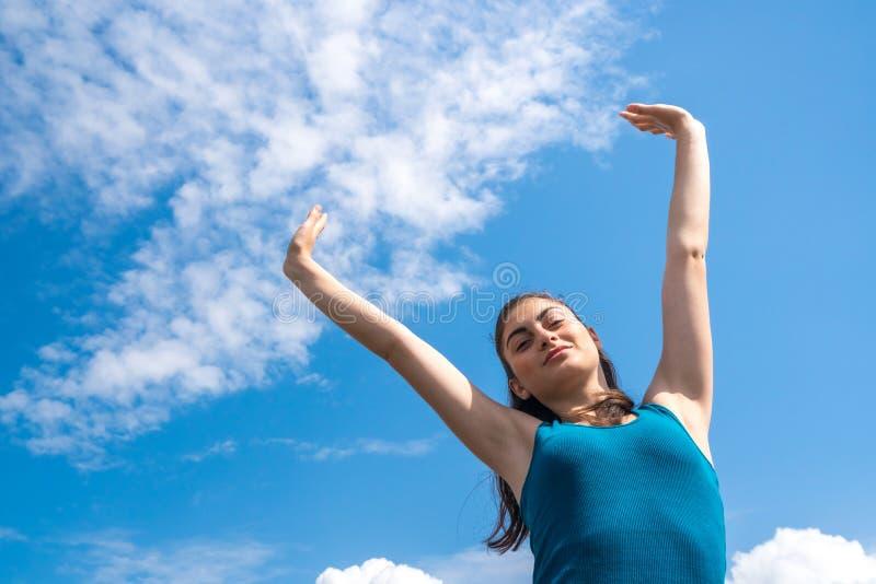 蓝天背景的美丽的体育女孩在锻炼以后 免版税库存图片